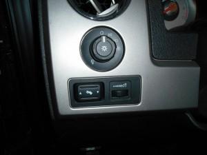 ручка управления светом, кнопка регулировки педалей и правее регулятор яркости подсветки приборов
